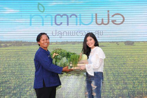 จรสพรรณ (ขวา) รับมอบชุดผักจากอัศจรรย์ (ซ้าย) เกษตรกรในกิจกรรมฝากปลูก