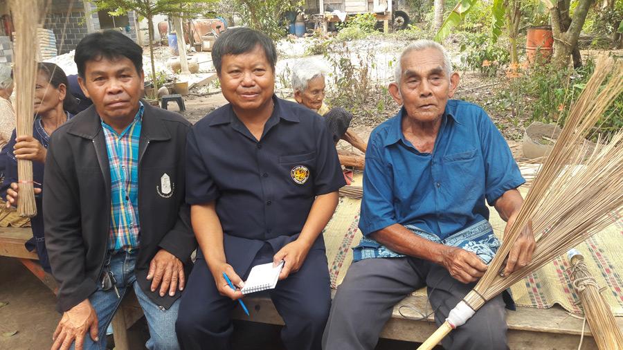 คนกลางคือกำนันสุวรรณ โด่กระโทก กับอีกคนคือรองนายก อบตลุงเขว้า กำลังชื่นชมผลงานจักสานทำไม้กวาดของลุงพัฒน์ เยี่ยมโคก ผู้อาวุโสแห่งชุมชนวัย 91 ปี