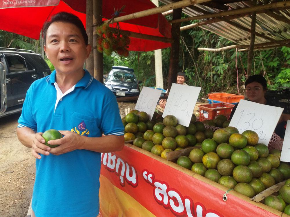 คุณสมชาย กับผลผลิตส้มโชกุนที่วางขายทางเข้าสวน